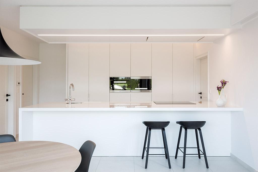 Totaalproject, keukentafel en twee zwarte barstoelen aan het keukeneiland met zicht op witte inbouwkasten