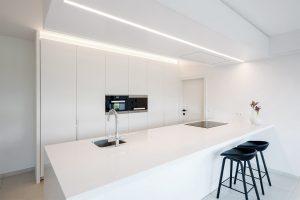 moderne zwarte barstoel aan het keukeneiland met elektrische kookplaat