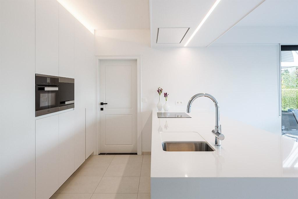 groot wit keukeneiland met composiet en hoge kraan
