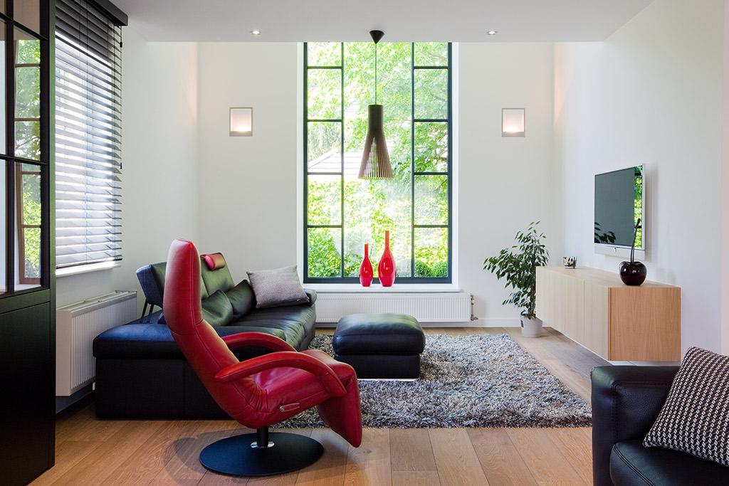 woonkamer rode fauteuil stalen kozijnen en vloerkleed