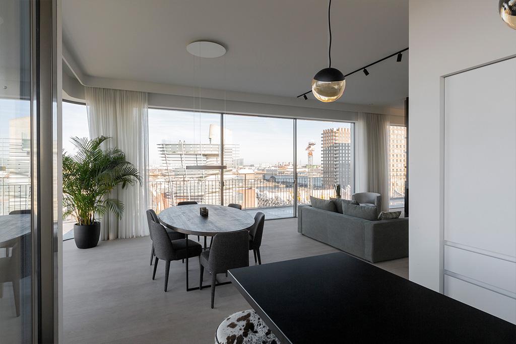 Woonkamer met eettafel, tweezitter en uitzicht over Antwerpen