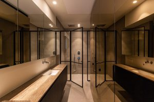 Badkamer met spiegel meubels en grote inloop douche
